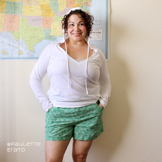 Woman in a white long sleeve hoodie and handmade shorts in green quilting cotton