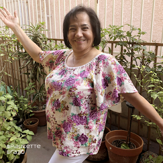 Smiling woman wearing a floral handmade Seamwork Loretta shirt in her garden patio