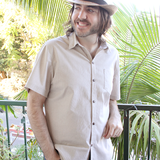 Man in handmade sandy colored short sleeved button up shirt leaning against a railing and wearing a straw fedora