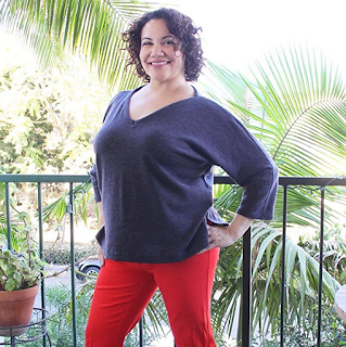 Curly haired brunette in a handmade grey v-neck sweater and red pants standing against a green railing
