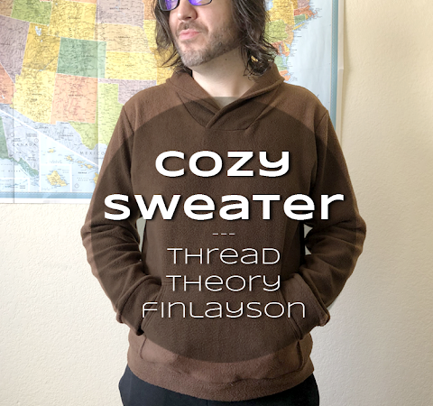 Ryan in a brown sweater, hands in the kangaroo pocket, standing in front of a map of the USA. Text overlay reads Cozy Sweater: Thread Theory Finlayson