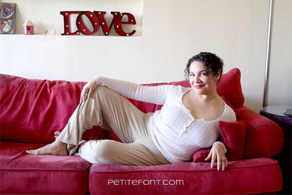 Woman in camel colored lounge pants and white long sleeve shirt laying on her side on a red couch, the word LOVE in the background and text overlay reads petite font .com