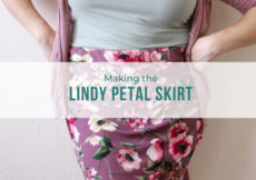 Close up image of a woman leaning against a wall with her hands on her hips, wearing a light green tank top, pink cardigan, and mauve floral skirt. Teal text overlay reads Making the Lindy Petal Skirt, Petite Font dot com