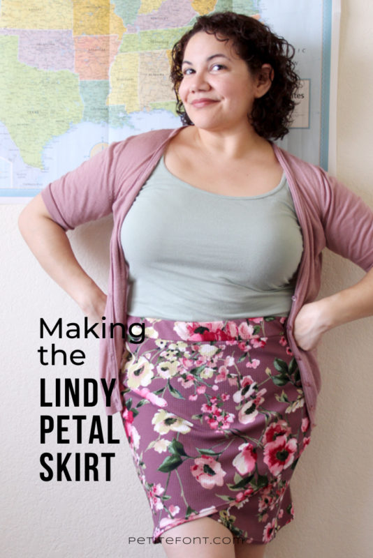 Image of a curly-haired Latina woman leaning against a wall with a US flag poster on it, her hands on her hips, wearing a light green tank top, pink cardigan, and mauve floral skirt. Black text overlay reads Making the Lindy Petal Skirt, Petite Font dot com