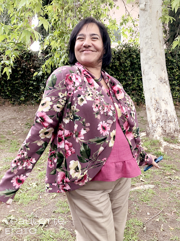 Image of a short haired Latina woman in a mauve floral Circle Cardi over a pink ruffled shirt and tan pants, standing in a grassy backyard