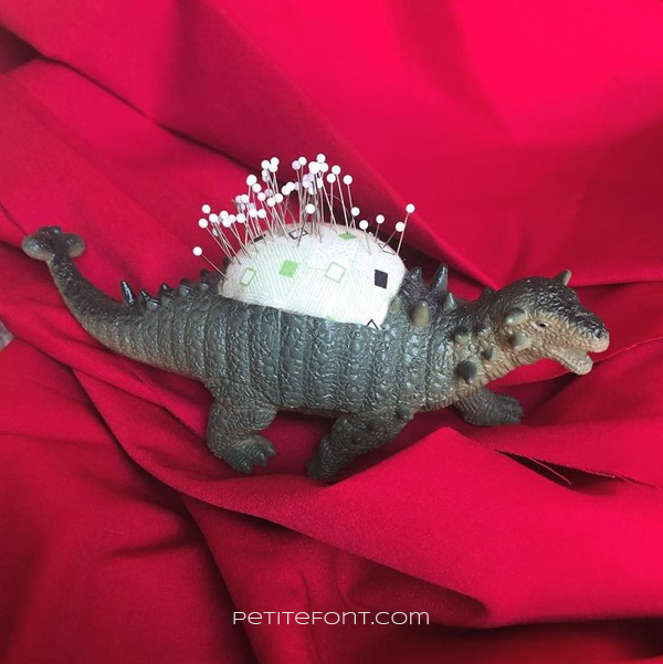 A pincushion made out of a plastic dinosaur against a red backdrop