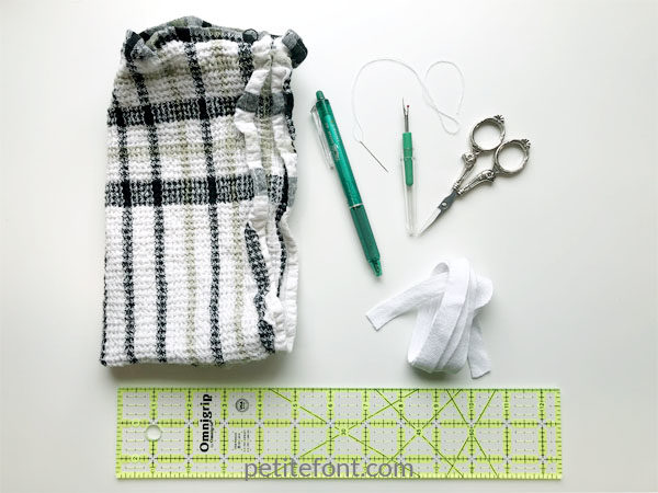 Materials for sew towel hanging loops: a towel, ruler, marking pen, needle and thread, seam ripper, scissors and twill tape or ribbon