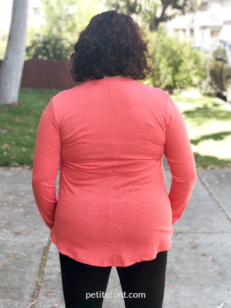 Back view of woman wearing a coral orange Laela Jeyne Samantha sweater