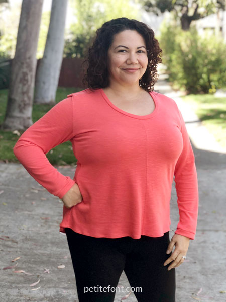 Front view of woman wearing a coral orange Laela Jeyne Samantha sweater with her hand on her hip