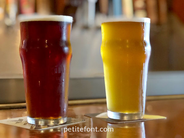 2 beer pint glasses on a bar top, one filed with dark ale, the other with a lighter colored ale enjoyed in Alamitos Beach, Long Beach