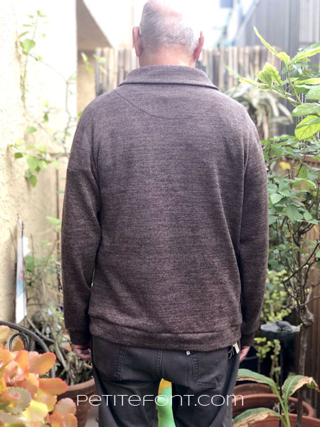 Back view of older bald Latino man in Finlayson sweater