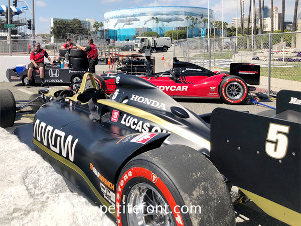 3 race cars parked behind concrete barriers