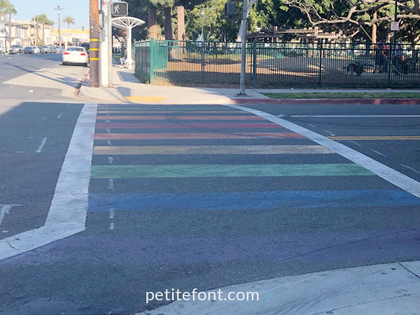 Sidewalk with rainbow colored stripes as seen in Alamitos Beach, Long Beach
