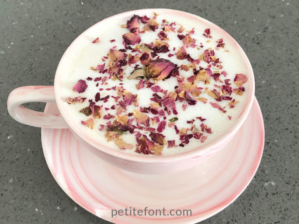 Rose latte in pink cup and saucer topped with rose petals served at Meant to Be Café in Alamitos Beach, Long Beach