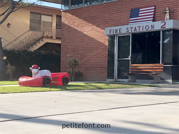 Fire station with plastic race car and fake sheep on front lawn in Alamitos Beach, Long Beach
