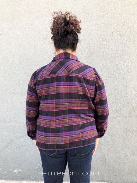 Back view of a woman in a flannel shirt against a grey wall