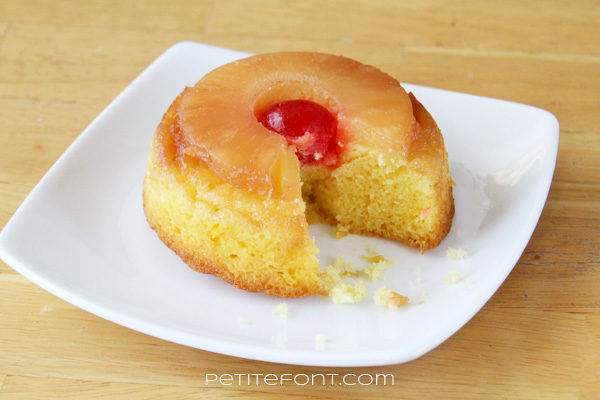 Single round serving of pineapple upside down cake with a bite missing, on a white plate, topped with a cherry