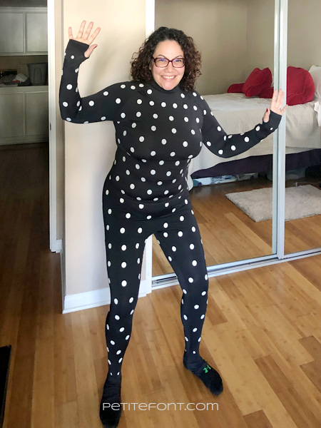 Woman in stretchy ZOZO suit (stretchy black body suit covered in white polka dots) smiling at camera with her hands up
