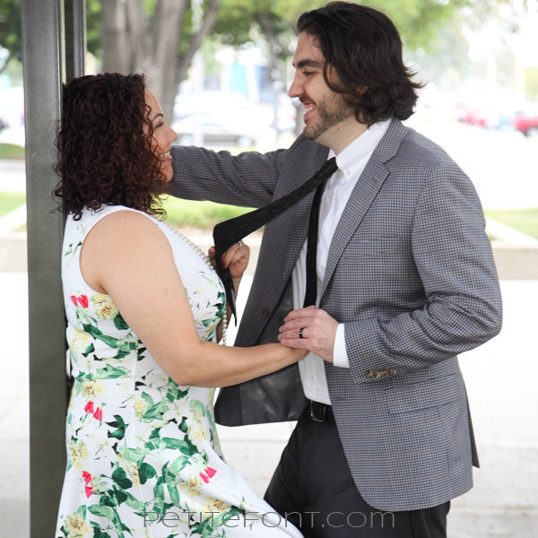 Woman leaning against a pole smiling while tugging at a man's tie as he smiles back at her