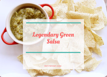 White platter with tortilla chips around a red bowl filled with green salsa with white box overlay and red text that reads Legendary Green Salsa petite font dot com