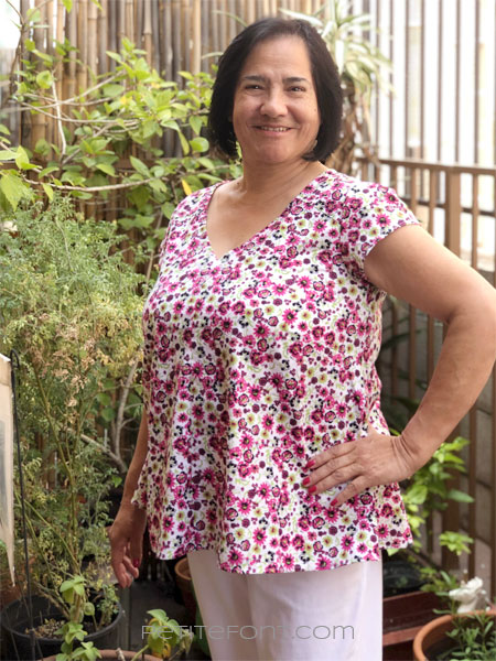 A woman with short black hair modeling New Look 6414 sewing pattern in floral quilting cotton, has her left hand on her hip and a big smile on her face
