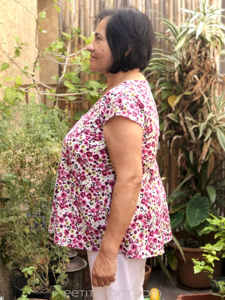 Side view of a woman with short black hair modeling New Look 6414 sewing pattern in floral quilting cotton.