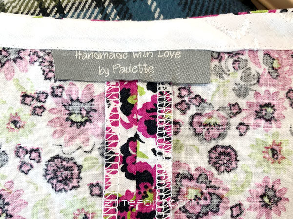Inside view of the back neckline of New Look 6414 sewing pattern finished with white bias binding and a clothing label inserted