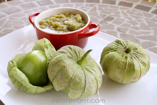 Red bowl filled with green salsa on a white platter with 3 whole tomatillos