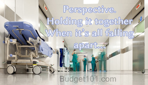 Looking down the hallway of a hospital with people in green scrubs down the hall, a gurney parked off to the left, white text overlay reads Perspective--holding it together when it's all falling apart. Budget101 dot com
