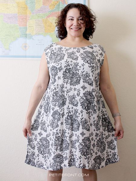 Curly haired woman in a handmade black and white Kenedy dress standing in front of a wall map of the USA