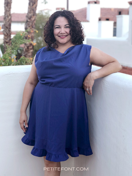 Curly haired brunette in a handmade blue Colette Myrtle dress with added hem ruffle, leaning against a white adobe wall and palm trees in the background. Text at bottom reads petite font dot com.