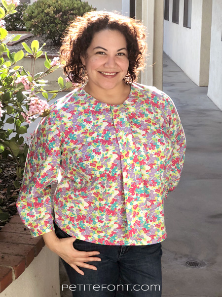 Curly haired woman with one hand behind her back and another on her hip smiling at the camera in a bright floral Laela Jeyne Cosette made in quilting cotton
