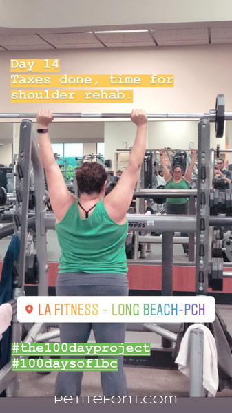 Image of a woman in a gym squat rack lifting a barbell over her head. Text overlay reads Day 14 Taxes done, time for shoulder rehab. LA Fitness-Long Beach-PCH hashtag the 100 day project hashtag 100 days of lbc Petite font dot com