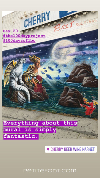 Image of an outdoor mural of a cat with angel wings and narwhal horn sitting on a rock next to a winged woman wings on her head, its tail in the water as blue birds fly away. A full moon in background behind lavender clouds. Text overlay reads Day 20 hashtag the 100 day project hashtag 100 days of lbc, Everythign about this mural is simply fantastic. Cherry Beer Wine Market. Petite font dot com.