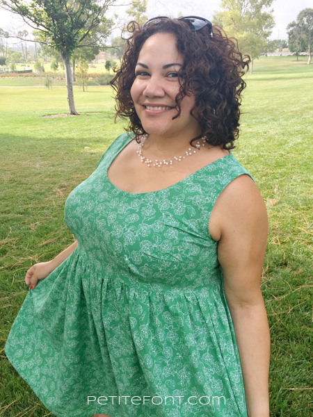 Curly haired woman in a sleeveless handmade green dress smiling, the dress is a hack of the French Navy Olra and Cashmerette Upton both great patterns for quilting cotton.