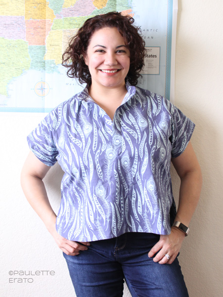 Curly haired woman leaning against a wall with a map of the USA wearing a handmade blue Closet Case Patterns Kalle cropped shirt made in designer quilting cotton