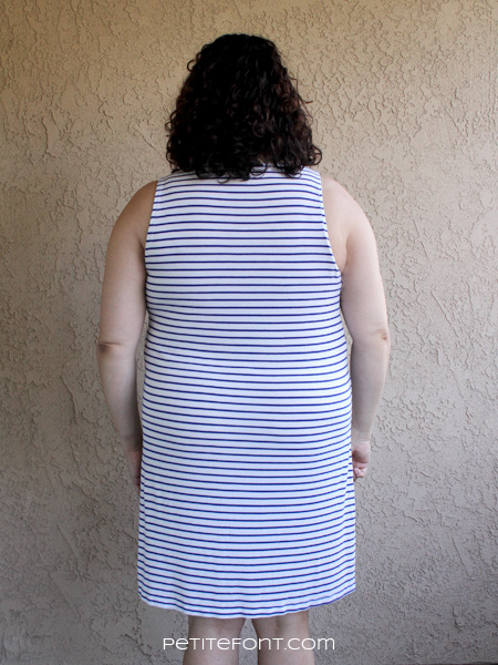 Back view of curly haired brunette in a striped blue and white knit tank dress based on McCall's 6744 pattern. Text at bottom reads petite font dot com.