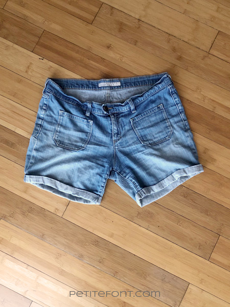 Weathered denim shorts flat lay on wood floor