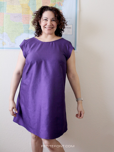 Curly haired woman in a handmade purple taffeta Kenedy dress standing in front of a wall map of the USA