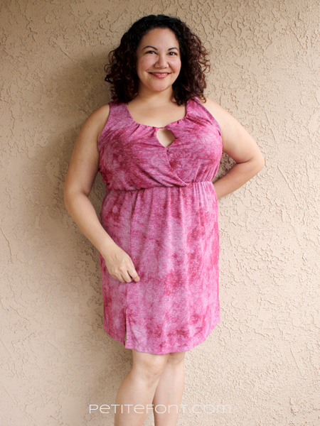Curly haired brunette in the Best Summer Dress Patterns for Knits #2, a sleeveless red keyhole knit dress leaning against a stucco wall with one hand behind her back
