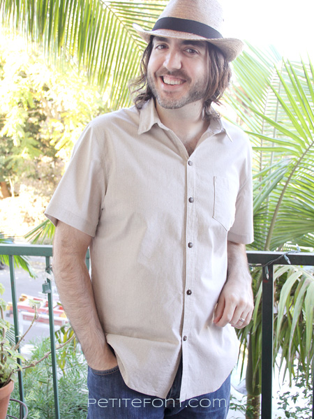Man leaning against a railing wearing a straw hat and button up short sleeved shirt