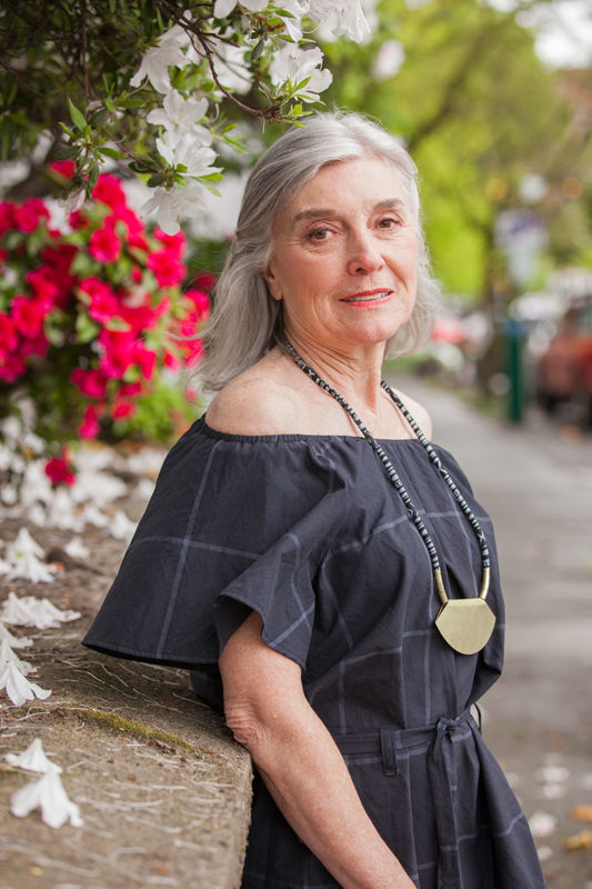 Marketing image from Seamwork Loretta pattern or older woman wearing an off-shoulder black tunic and statement necklace