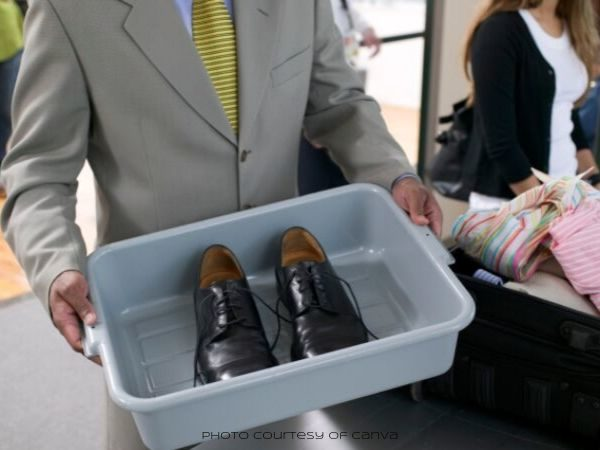 Headless man in a suit holding a bin with his dress shoes while in an airport security line
