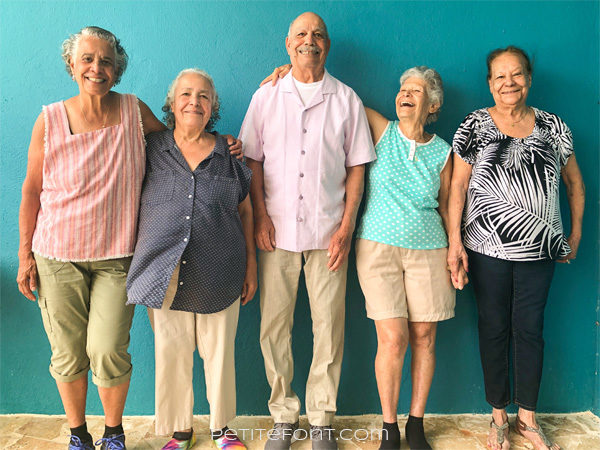 5 siblings ages 74-86 laughing against a turquoise wall in Puerto Rico
