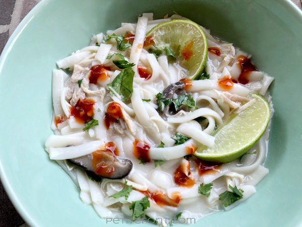 Close-up of easy Thai chicken noodle soup, or tom kha gai, in a green bowl