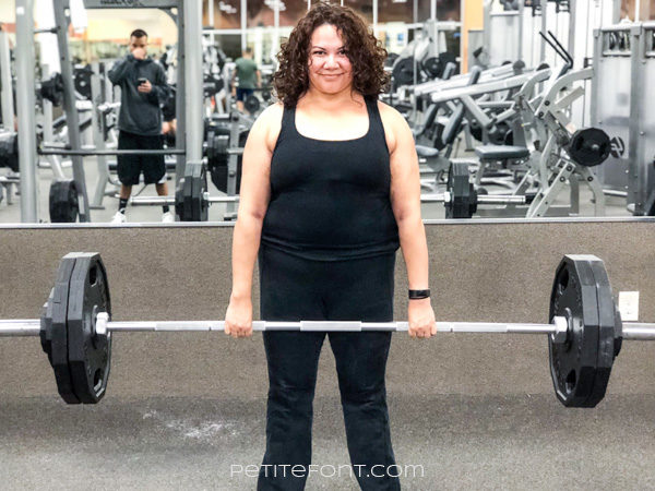 Curly haired woman at the gym dressed in black deadlifting 250 pound barbell