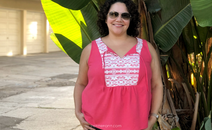 Front view of a smiling curly haired Latina woman wearing a sleeveless pink silk and lace handmade Phoenix blouse