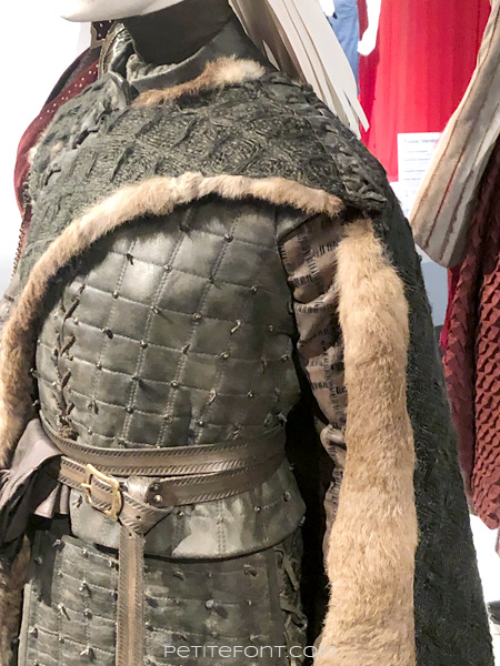 Detail of asymmetric shawl on mannequin modeling Arya Stark's warrior outfit in the Game of Thrones costumes exhibition at FIDM Museum