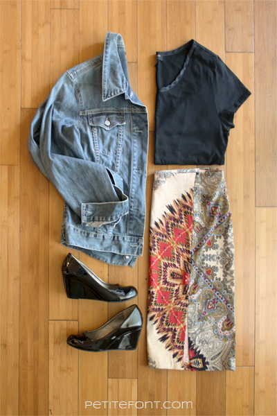 Flatlay image of how to style a jean jacket for a business casual office: jean jacket, black blouse, pencil skirt with an Aztec print, black patent leather wedge heels