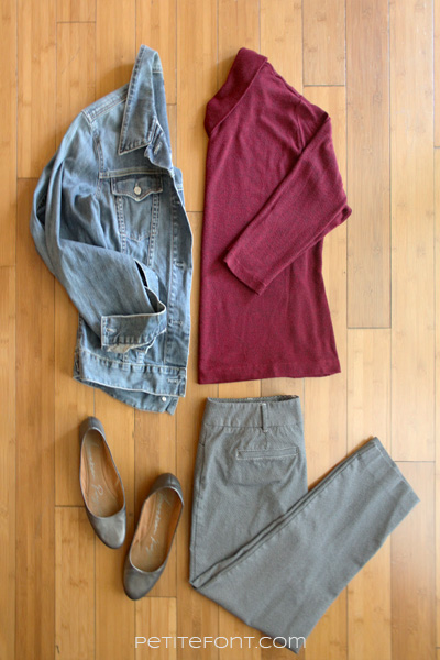 Flatlay image of how to style a jean jacket for a business casual office: jean jacket, red turtleneck with 3/4 length sleeves, slim fit pants, and grey ballet flats